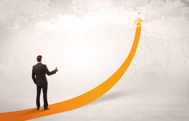 A young adult salesman standing on a big orange arrow pointing up in a bright empty space concept-2