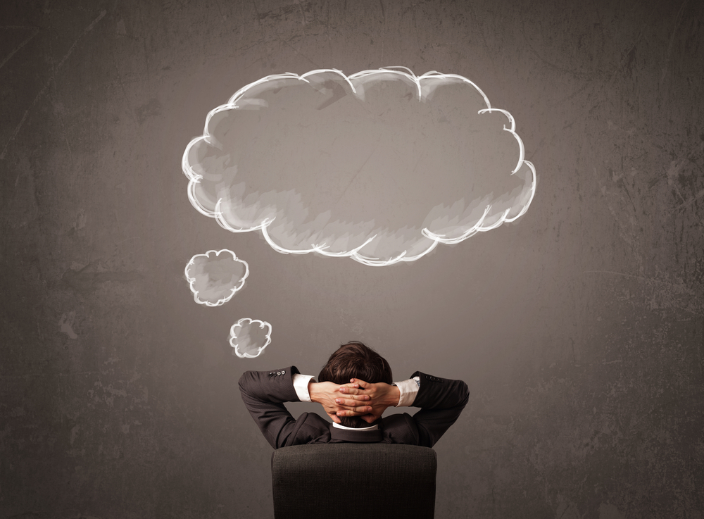 Young businessman sitting in office chair in front of a wall with cloud thought sketched on a chalkboard above his head